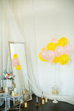 Colorful ballons with flowers on the white wall. Pink and yellow ballons with flowers on the white wall in studio Royalty Free Stock Images