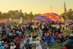 Half inflated hot air balloon in middle of huge crowd stock photo