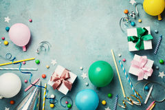 Colorful balloon, present or gift box, confetti, candy and streamer on vintage turquoise table top view. Birthday background.