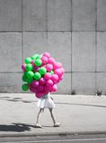 Colorful balloons. Girl walking with bunch of air-balloons royalty free stock images