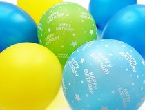 Colorful balloons in blue yellow apple green and turquoise with happy birthday text. With a white background royalty free stock image