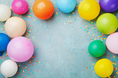 Colorful balloons and confetti on blue table top view. Festive or party background. Flat lay style. Birthday greeting card.