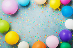 Colorful balloons and confetti on turquoise table top view. Birthday, holiday or party background. Flat lay style.