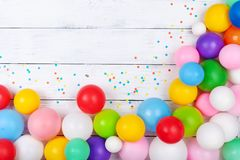 Colorful balloons and confetti on white table top view. Festive or party background. Flat lay. Birthday greeting card. Colorful balloons and confetti on white stock image