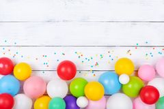Colorful balloons and confetti on white table top view. Festive or party background. Flat lay. Birthday greeting card. Colorful balloons and confetti on white royalty free stock photos