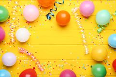 Balloons with confetti. Colorful balloons with confetti on yellow wooden table stock photo