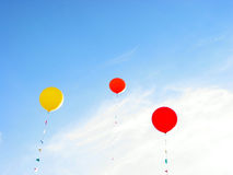 Colorful balloons flying in blue sky. On a bright summer day Royalty Free Stock Image