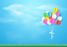 Colorful balloons flying over grass. Paper art and craft style. Colorful balloons flying over grass on blue sky background. Paper art and craft style Stock Image