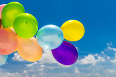 Colorful balloons flying in the wind. Bunch of colorful balloons flying over tropical ocean Royalty Free Stock Image