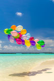 Colorful balloons flying in the wind. Bunch of colorful balloons flying over tropical ocean Royalty Free Stock Photography