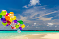Colorful balloons flying in the wind. Bunch of colorful balloons flying over tropical ocean Royalty Free Stock Photos