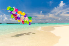 Colorful balloons flying in the wind. Bunch of colorful balloons flying over tropical ocean Stock Photos