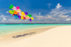 Colorful balloons flying in the wind. Bunch of colorful balloons flying over tropical ocean Stock Images