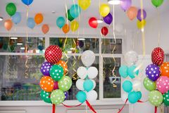 Colorful balloons hang under the white ceiling. stock photography