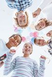 Colorful balloons hanging above kids. Holding the strings and enjoying themselves while looking down Stock Photo