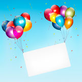 Colorful balloons holding up a cloth white banner. Royalty Free Stock Images