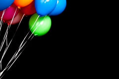 Colorful balloons over black wall background Stock Images