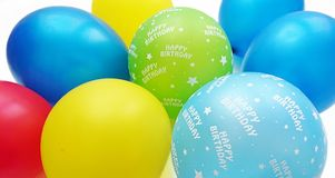 Colorful balloons in red blue yellow apple green and turquoise with happy birthday text. With a white background stock image
