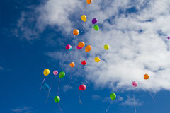 Colorful balloons in the sky. Lots of colorful balloons in the sky on a background of white clouds Stock Photos