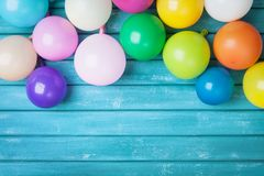 Colorful balloons on turquoise wooden table top view. Birthday celebration or party background. Festive greeting card.