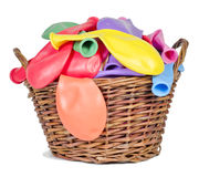 Colorful balloons  in a wicker basket. Colorful balloons in large numbers in a wicker basket on the table Royalty Free Stock Image