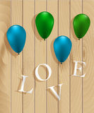Colorful balloons on wooden texture. Love word from wooden texture. Colorful balloons on wooden texture with love word Stock Photography