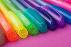 Colorful ballpoint pens on color background. Closeup of colorful ballpoint pens on color background stock photography