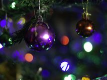 Colorful balls on a green christmas tree at led lights bokeh stock photography