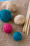 Colorful balls and needles lying on beige Royalty Free Stock Images