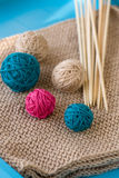 Colorful balls and needles lying on beige Stock Image