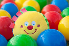 Colorful balls with smiling face toy in the middle. Colorful plastic balls with smiling face toy in the middle Stock Images