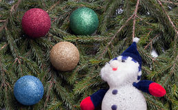 Colorful balls and snowman lying on spruce branches. Stock Photos
