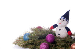 Colorful balls and snowman lying on spruce branches. Royalty Free Stock Image