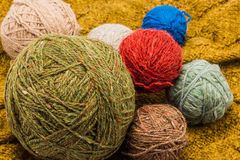 Colorful balls of woolen threads. On a background of knitted sweaters Royalty Free Stock Photography