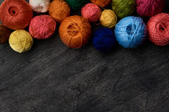 Colorful balls of yarn on wooden background. Colorful balls of yarn on wooden background of chalk board Stock Image