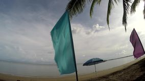 Colorful banner flags and Umbrella Parasol line on tropical empty sandy beach. Tracking shot stock footage