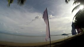 Colorful banner flags and Umbrella Parasol line on tropical empty sandy beach. Tracking shot stock video