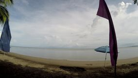 Colorful banner flags and Umbrella Parasol line on tropical empty sandy beach. Tracking shot stock video footage