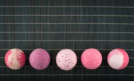 Colorful bath bombs arranged in a row on a bamboo placemat. Colorful pink bath bombs arranged in a row on a black bamboo placemat royalty free stock image