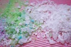 Colorful bath salt on pink background. stock photos