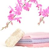 Colorful bathroom set with natural soap. A bathroom set with three towels of different color, a bar of natural soap and a decorative pink orchid Royalty Free Stock Photography