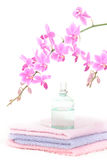 Colorful bathroom set with perfume bottle. A bathroom set with three towels of different color, a perfume bottle and a decorative pink orchid Royalty Free Stock Images