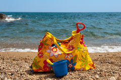 Colorful beach bag. Colorful yellow vacation beach bag with plastic toys Royalty Free Stock Image