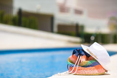 Colorful beach bag, straw hat and airplane model. Colorful stripe bag, sunglasses, and straw white hat on summer vacation near pool Stock Image