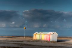 Colorful beach bathing cabins. Multicolored bathing wooden huts lined up on the deserted beach of Berck-sur-Mer, France, in the early morning Royalty Free Stock Image
