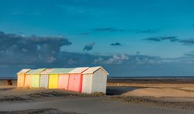 Colorful beach bathing cabins. Multicolored bathing wooden huts lined up on the deserted beach of Berck-sur-Mer, France, in the early morning Stock Photos