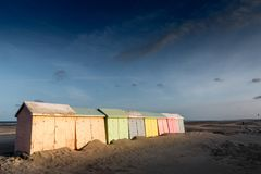 Colorful beach bathing cabins. Multicolored bathing wooden huts lined up on the deserted beach of Berck-sur-Mer, France, in the early morning Royalty Free Stock Images