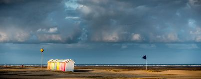 Colorful beach bathing cabins. Multicolored bathing wooden huts lined up on the deserted beach of Berck-sur-Mer, France, in the early morning Stock Photo