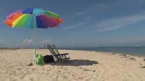 Colorful beach chairs and umbrella on beach stock video