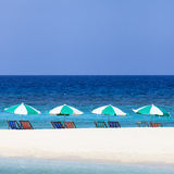 Colorful beach chairs and umbrellas on the beach Stock Photos